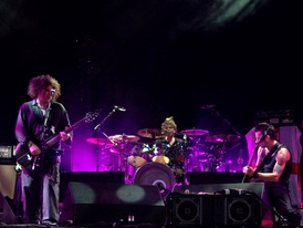 The Cure in concert in 2004. From left to right: Robert Smith, Jason Cooper, Simon Gallup.