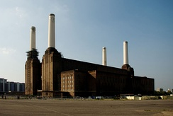 Colour picture of a power station factory with four tall white chimneys. The image was taken on a sunny day. The sky is blue and the building is brown.