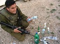 An IDF soldier shows materials used to prepare Molotov cocktails, which were found on two Palestinian youths near the Huwara checkpoint.