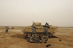 U.S. Soldiers fire the M120 Mortar system out of an M113 at Camp Taji, Iraq, 2009.