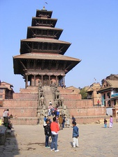 "Clockwise from top-left: (a) Nyatapola, a five storied pagoda in Bhaktapur, bejewelled with characteristic stone, metal and wood craftsmanship, has survived at least four major earthquakes.[300] Pagodas, now an indispensable part of East Asian architecture, are conjectured to have been transmitted to China from Nepal. (b) Nepali stonecraft in a community water spout (c) A traditional Newar ""Ankhijhyal"" window in the form of a peacock"