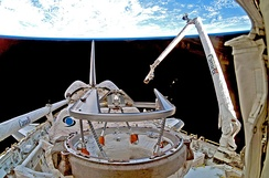 "A shuttle in space, with Earth in the background. A mechanical arm labelled ""Canada"" rises from the shuttle."