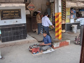 A boot polisher on a railway platform in Mumbai, India.