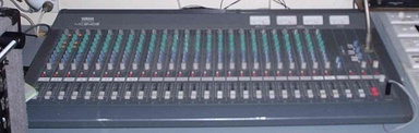 Yamaha 2403 audio mixing console in a 'live' mixing application. Each column of knobs controls the volume, tone, and other elements for a single channel (e.g. a microphone being used by a singer).