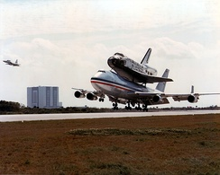Deke Slayton flying T-38 (far left) during the return of  B 747 SCA airplane with Space Shuttle Columbia on board just before touchdown at Kennedy Space Center, March 1979