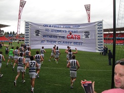 Geelong players prepare to break a banner, which is created by its supporters, before a match against Greater Western Sydney in June 2013.