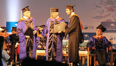"Student receiving academic degree from Azim Premji during a Graduation ceremony in ISB. Adi Godrej in the background. Recipient and donors in ""convocation dress""."