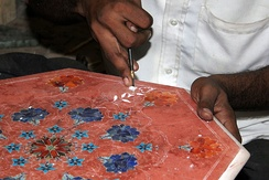 An Agra craftsman working with marble stone inlays. The marble is coloured red to give contrast while working.