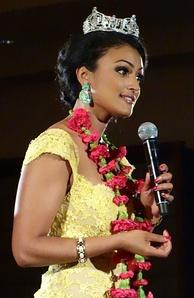Davuluri speaking, wearing her Miss America tiara, large earrings and a long necklace of red flowers