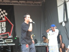 Knee high portrait of male in his twenties, facing right wearing a black t-shirt and jeans, singing into microphone. Young man covering his ears and three people listening in background behind him.