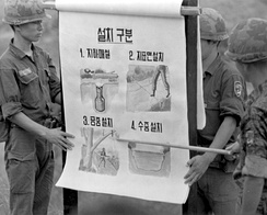 Vietnam War: Republic of Korea Armed Forces soldiers show Vietnamese villagers types of Viet Cong booby traps.