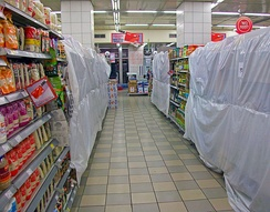 A narrow supermarket aisle, under strip fluorescent lighting, with sections blocked off by white plastic sheeting