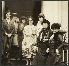 Photograph of (left to right) Alice Paul, Sue White, Florence Boeckel, Anita Pollitzer (center, holding hat), Mary Winsor, Sophie Meredith, and Mrs. Richard Wainwright of the National Woman's Party standing on front steps in front of new national headquarters building, across from the U.S. capitol in May 1922