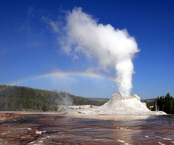 Eruption of Castle Geyser, Yellowstone National Park, with double rainbow seen in the mist