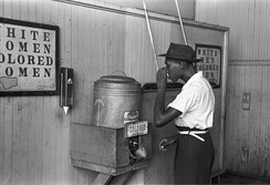 "A drinking fountain from the mid-20th century labelled ""Colored"" with a picture of an African-American man drinking"