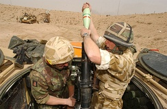 Two soldiers with a mortar gun—one loading and the other aiming