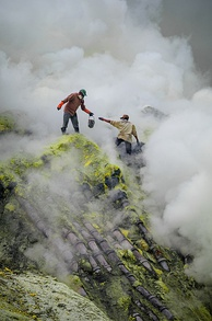 Traditional sulfur mining at Ijen Volcano, East Java, Indonesia. This image shows the dangerous and rugged conditions the miners face, including toxic smoke and high drops, as well as their lack of protective equipment. The pipes over which they are standing are for condensing sulfur vapors.