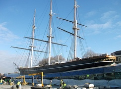 Cutty Sark in February 2012, repairs nearing completion. The temporary cover which surrounded the ship during repair has been removed although workmen can still be seen on deck and in the rigging where not all yards have been replaced. Work was underway around the dock to lay new paving.