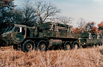 An early promotional image of a M977 HEMTT and trailer; payload are MLRS reloads