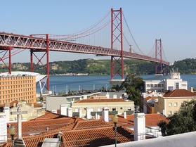 View of the 25 de Abril Bridge, formerly Bridge Salazar, from Chapel of Santo Amaro, with Christ the King in the background.
