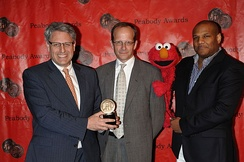 Sesame Workshop CEO Gary Knell, Executive Vice-President Terry Fitzpatrick, and puppeteer Kevin Clash (with Elmo) at the 69th Annual Peabody Awards, in 2010