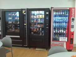 A full line of vending machines in a hospital cafeteria, including machines for drinks, snacks, and microwaveable foods