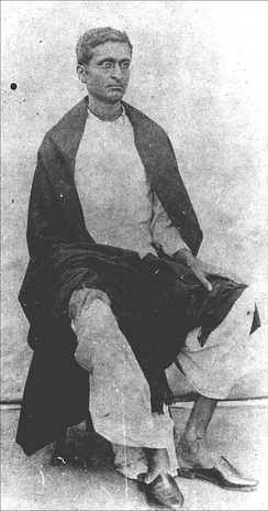 A photo of a sitting young Indian man wearing spectacles and looking to the right