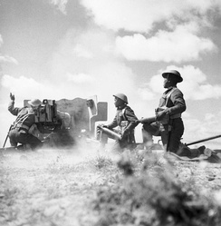 Gurkhas in action with a six-pounder anti-tank gun in Tunisia, 16 March 1943.