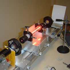 A helium–neon laser demonstration. The glow running through the center of the tube is an electric discharge. This glowing plasma is the gain medium for the laser. The laser produces a tiny, intense spot on the screen to the right. The center of the spot appears white because the image is overexposed there.