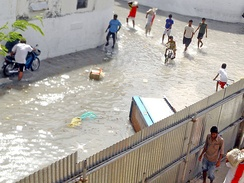 People in Malé removing sand bags from a nearby construction site, to be used as a barrier to protect their homes from the flood, shortly after being hit by the tsunami generated by the 2004 Indian Ocean earthquake.