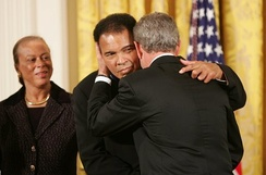 As Mrs. Lonnie Ali looks on, President George W. Bush embraces Muhammad Ali after presenting him with the Presidential Medal of Freedom on November 9, 2005, during ceremonies at the White House.