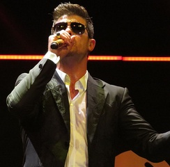 Robin Thicke wearing sunglasses and holding a microphone.