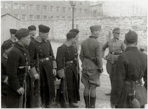 Stroop Report Trawniki shooters during the Warsaw Ghetto Uprising, with Jürgen Stroop (on the right), 1943 at the Umschlagplatz, with Stawki 5/7 in the back. Their military coats came from the Allgemeine-SS surplus no longer used by the German SS.[14]