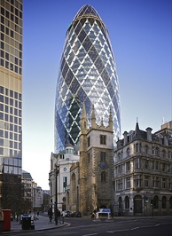 "30 St Mary Axe, also known as ""the Gherkin"", towers over St Andrew Undershaft. Modern architecture juxtaposed by historic architecture is seen often in London"