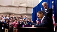 President Barack Obama signs the ARRA into law on February 17, 2009 in Denver, Colorado. Vice President Joe Biden stands behind him.