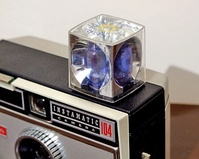 Flashcube fitted to a Kodak Instamatic camera, showing both unused (left) and used (right) bulbs