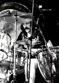 A black and white photograph of John Bonham playing drums
