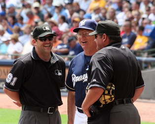 A man in a navy blue baseball jersey standing on a field between two men in black umpiring outfits