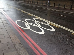Olympic rings marked on a street, indicating that the lane was reserved for the use of Olympic athletes and staff.