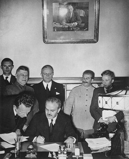 With German Foreign Minister Joachim von Ribbentrop and Soviet Communist Party leader Joseph Stalin looking on, V. M. Molotov signs the non-aggression treaty on behalf of the Soviet Union, August 23, 1939.