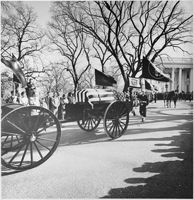 "A limbers and caissons bearing the casket of United States President John F. Kennedy seen moving down the White House drive on the way to St. Matthew's Cathedral on November 25, 1963. A color guard holding the presidential colors, the flag of the President of the United States, and the riderless horse ""Black Jack"", follow behind."
