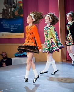 Irish dancers in Irish dancing costumes, which often feature lace or an embroidered pattern copied from the medieval Irish Book of Kells.[23]
