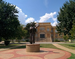 A statue of a woman in Native American costume in front of a yellow brick three-story building.