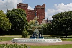 Ornamental fountain in circular pool surrounded by grassy areas. In the background it a red brick building.
