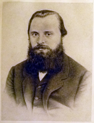 A man in his late 20s or early 30s with dark hair and a bushy beard, wearing a dark coat, dress shirt and tie.