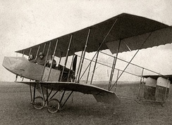 A 1912 Farman HF.20 biplane with single acting ailerons hinged from the rear spar. The ailerons hang down when at rest and are pushed up into position when flying by the force of the air, being pulled down by cable to provide control.