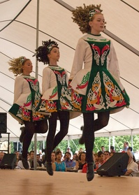 Irish stepdancers performing in school costumes and hard shoes