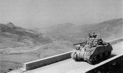 A U.S. Army Sherman tank moves past Sicily's rugged terrain in mid July 1943.