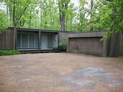 A brown modernist squarish house and garage is pictured