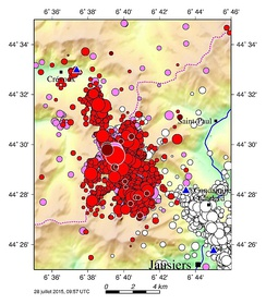 Ubaye earthquake swarmsComplete caption White: 2003–2004 swarm; pink: 2012–2015 swarm up to 2014-04-06; red: earthquakes as of 2014-04-07; pink and red lined up in white: epicentres of 2012-02-26 earthquake (M=4.3) and 2014-04-07 earthquake (M=4.8); brown: latest 20 earthquakes in July 2015, just before the map was drawn. Symbol size directly proportional to magnitude. Blue triangles show the 3 nearest seismic stations.[6]